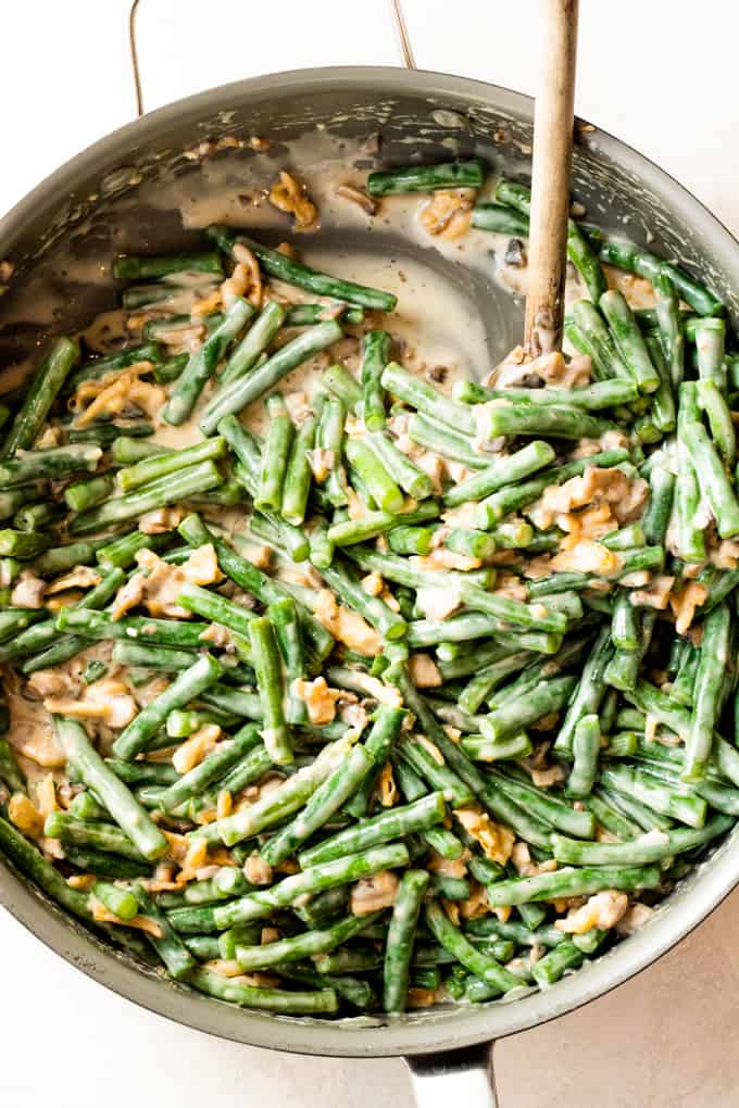 Large skillet filled with creamy green bean casserole ready to bake.