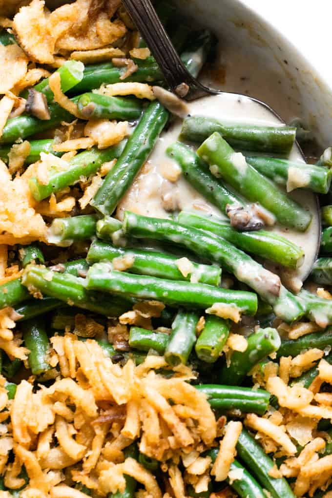 Spoon scooping up green beans in a creamy mushroom sauce.