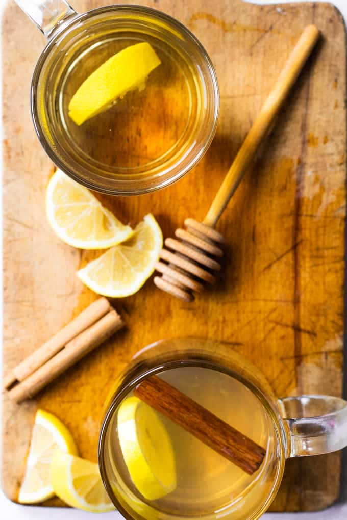 Overhead view of two hot toddy on a wooden board and lemon slices.