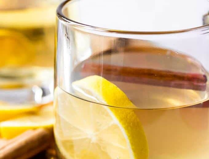 Hot Toddy with honey and Lemon in a glass mug garnished with a cinnamon stick.