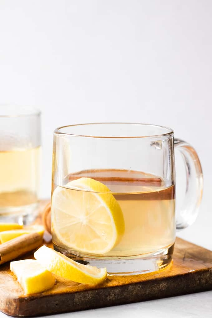 Hot toddy on a wooden board, garnished with lemon slice and a cinnamon stick.