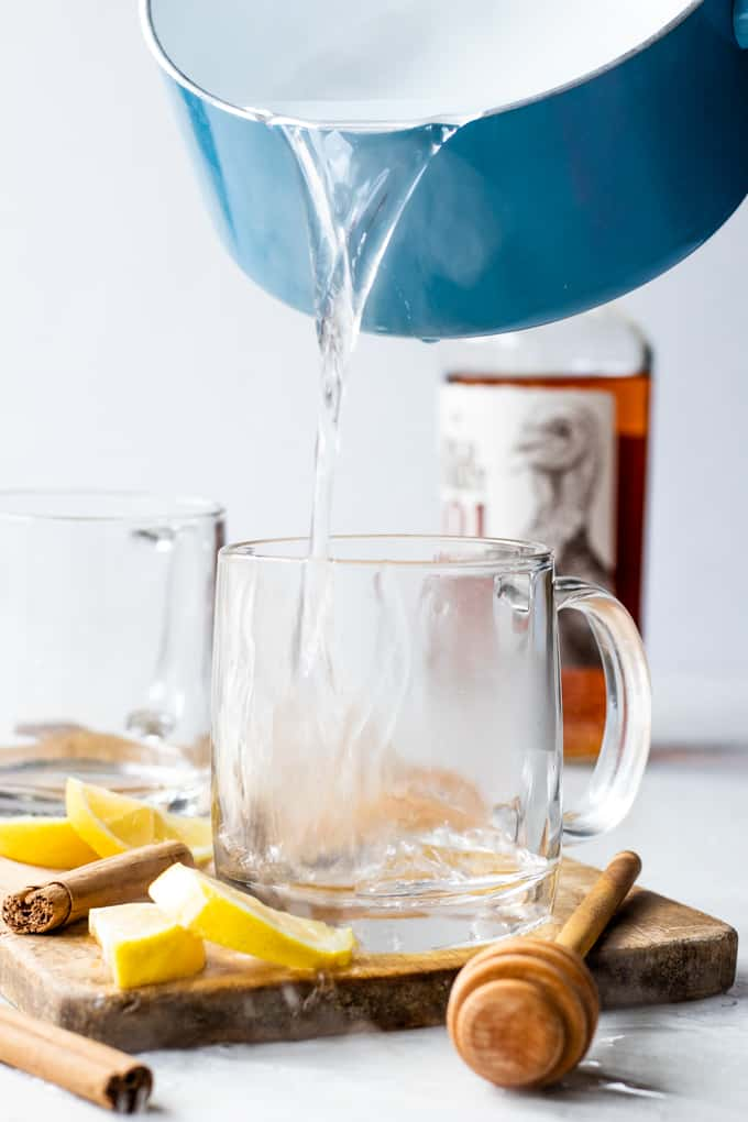 Pouring hot water into a glass mug for a hot toddy.