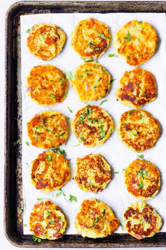 Mashed potato cakes laying on a baking sheet with paper towels, showing golden fried sides.