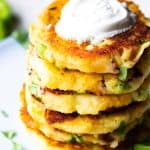 Loaded mashed potato cakes stacked and topped with sour cream.