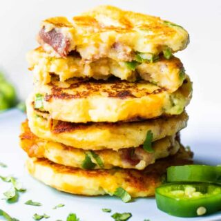 Stack of mashed potato cakes loaded with jalapeno, bacon and cheese.