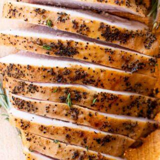 Sliced smoked turkey breast on a wood cutting board.