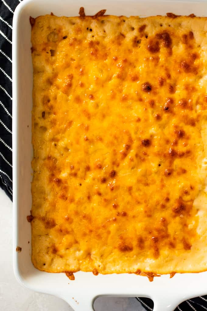 Baking dish filled with baked macaroni and cheese, showing browned bits of cheese on the top layer.