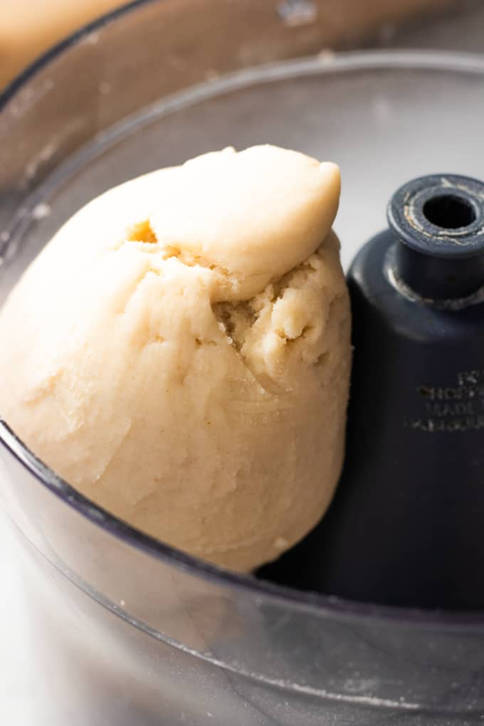 Ball of pie crust dough in a food processor.
