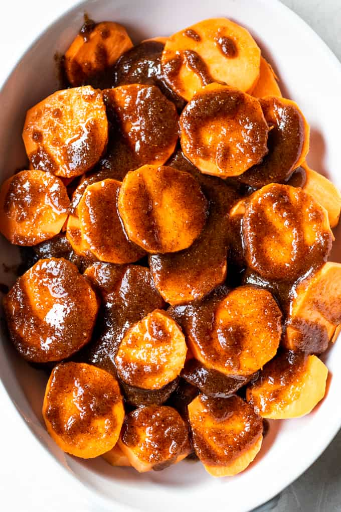 Brown sugar butter sauce poured over sliced sweet potato to make candied sweet potatoes.