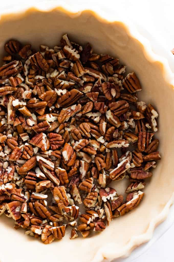 Chopped pecans in the bottom of a pie dish.