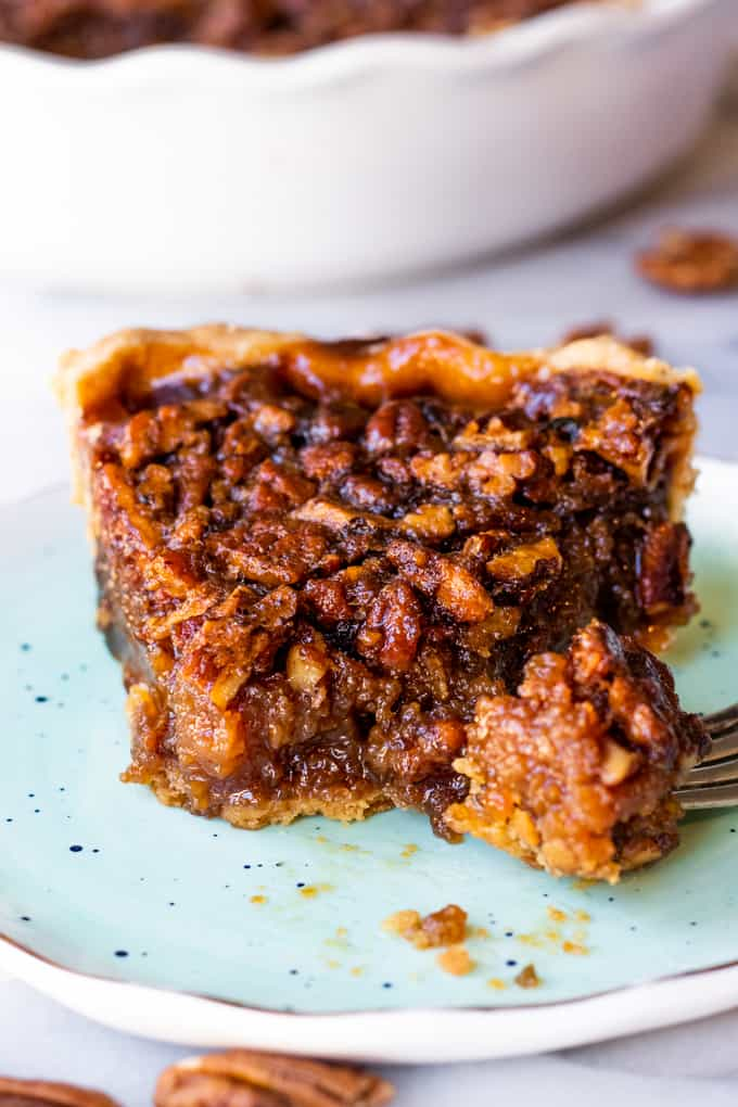 A slice of pecan pie on a dish.