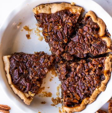 Pie dish with sliced pecan pie, a couple pieces have been removed.