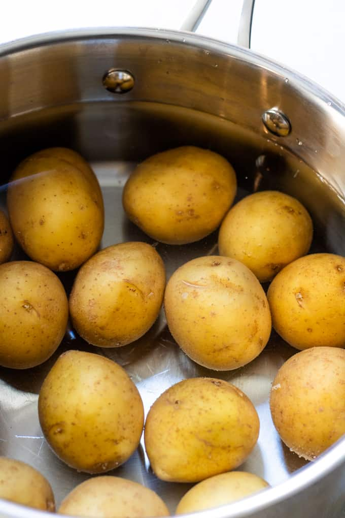 Saucepan filled with water and small gold potatoes.