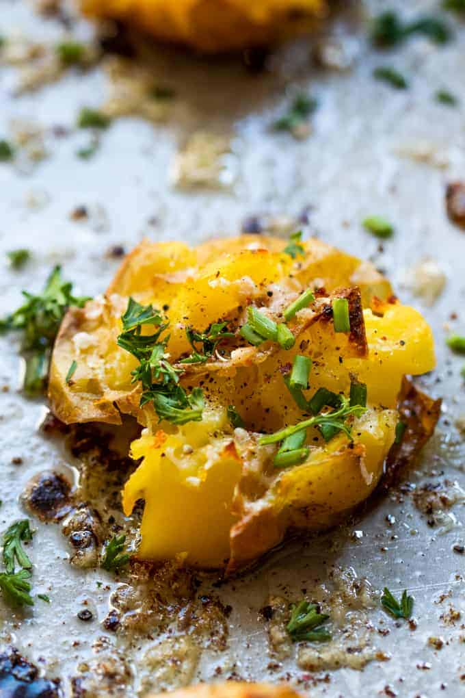 Close of of a baked smashed potato sprinkled with fresh parsley and chives.