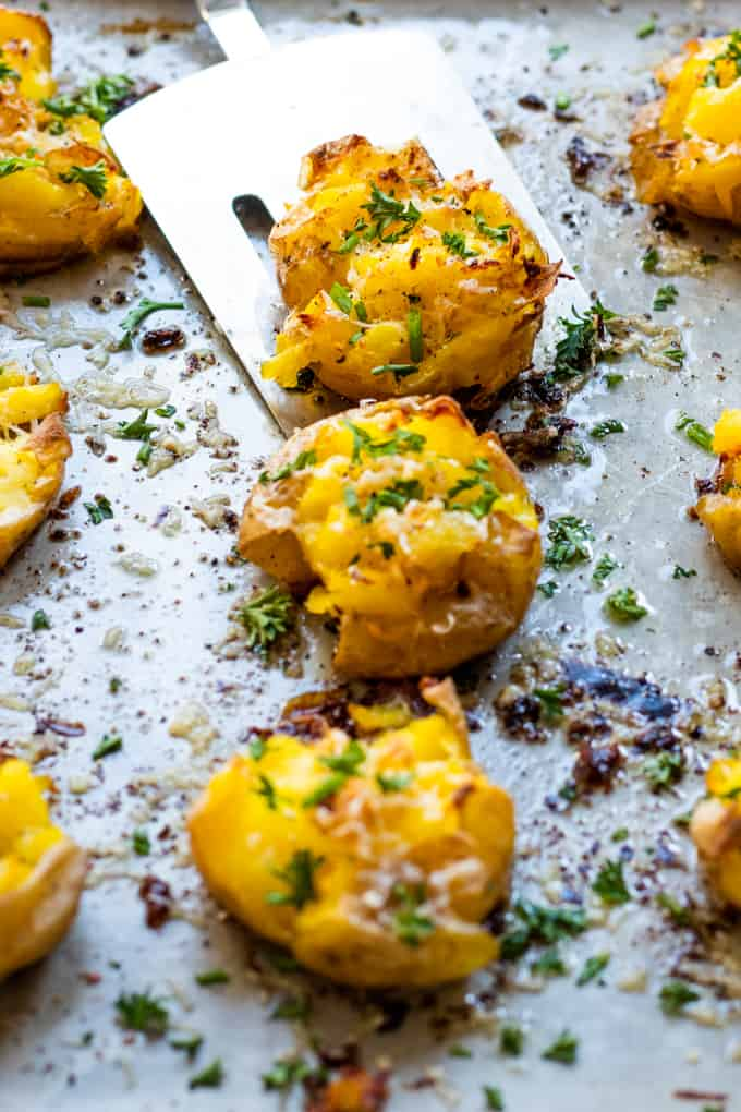 Smashed potatoes on a baking sheet being picked up with a spatula.