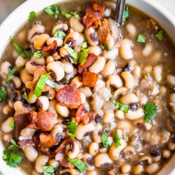 Texas style black eyed peas served in a bowl garnished with crisp bacon and diced cilantro.