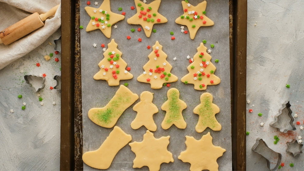 Sugar cookies being decorated with sprinkles ready to bake.