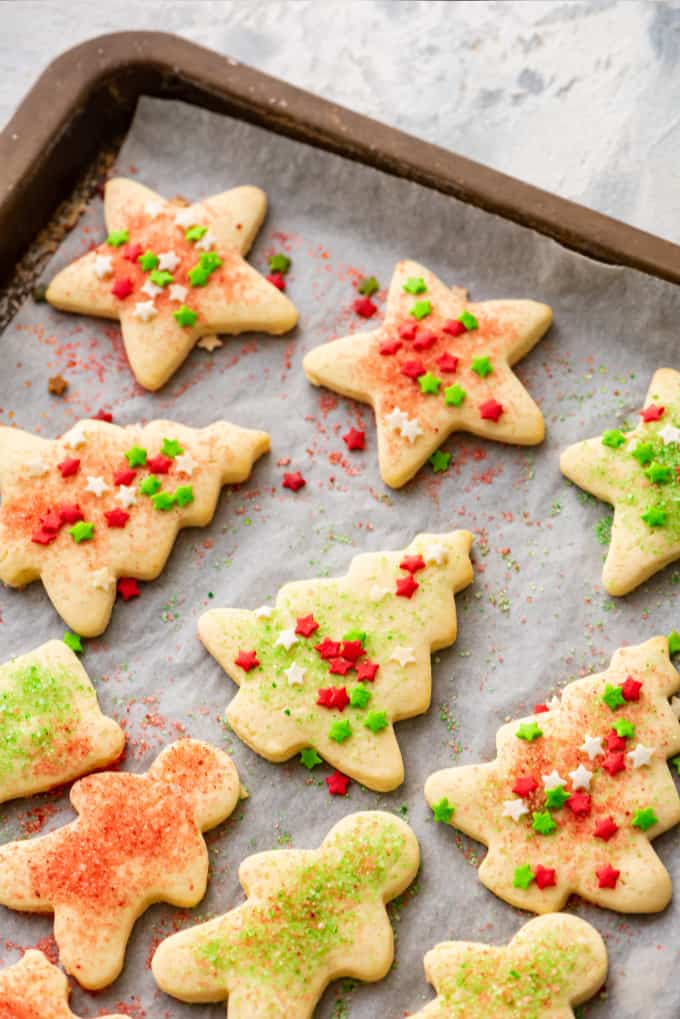 Cut out sugar cookies decorated with sprinkles, on a baking sheet.