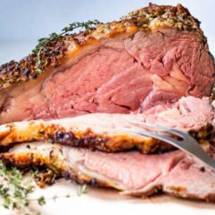 Slicing into a cooked prime rib that is rare in the center.