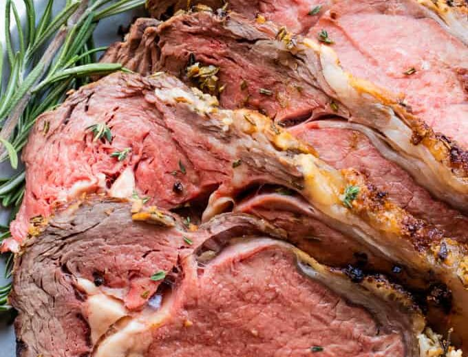Garlic herb prime rib sliced and laid on a plate garnished with fresh rosemary.