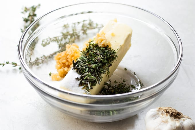 Ingredients needed to make garlic herb butter in a small glass bowl.