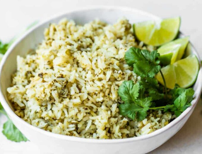 Bowl of green rice topped with cilantro and lime wedges.
