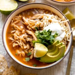 Bowl filled with white chicken chili and topped with cheese, sour cream and avocado.