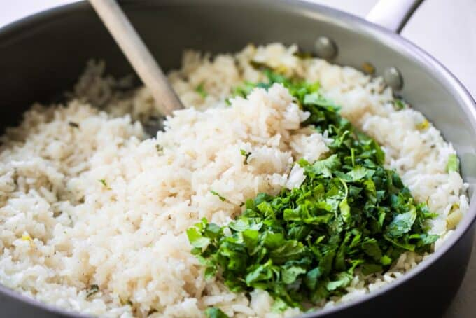Cooked fluffy white rice with fresh cilantro on top.