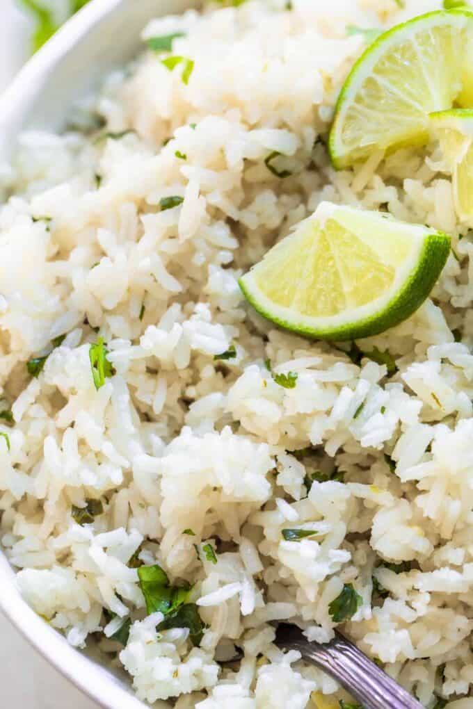 Fluffy white rice with cilantro and fresh lime wedges.