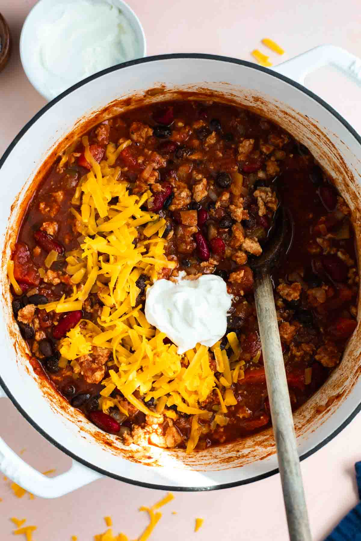 Pot filled with cooked turkey chili, topped with shredded cheese and sour cream.