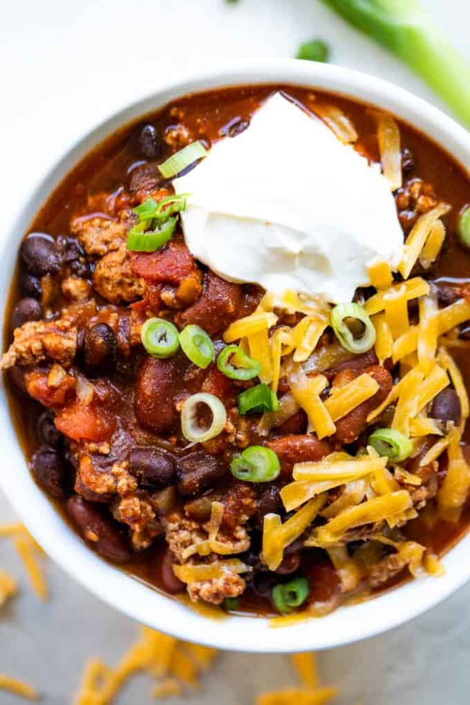 Bowl filled with turkey chili, topped with sour cream, onion and cheese.