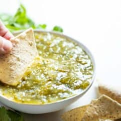 Chip dipping into a bowl of salsa verde.