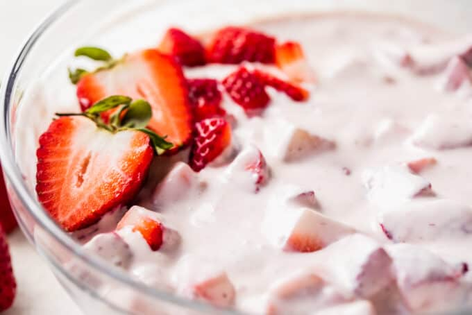 Glass bowl filled with strawberries in a homemade cream sauce, topped with diced strawberries.