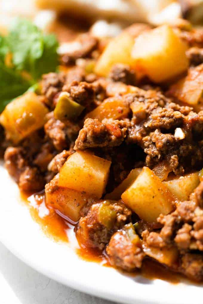 Mexican picadillo on a white plate with sauce pooling underneath.