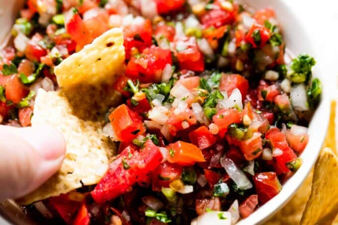 Chip dipping into a bowl filled with pico de gallo.