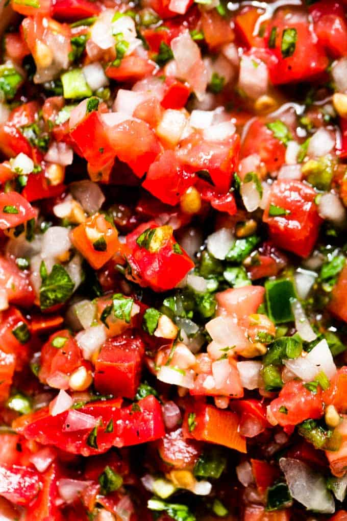 Up close view of pico de gall showing chunks of tomato, jalapeno and onion soaked in a lime juice.