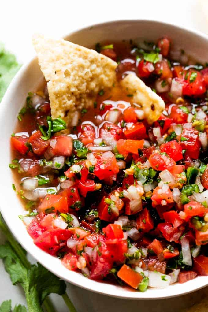 White bowl filled with pico de Gallo and a tortilla chip dipped in showing the juices.