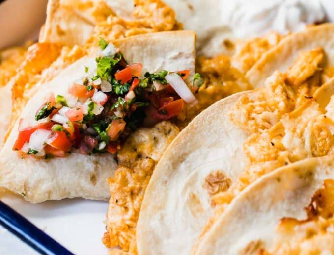 Tray filled with baked chicken quesadillas topped with fresh Pico de Gallo and extra sour cream.