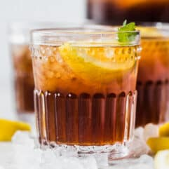 Glasses of sweet tea surrounded by ice and lemon wedges.