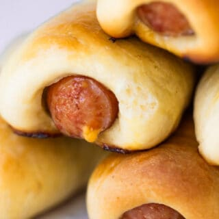 Stack of Texas Kolaches with cheese coming out of the sausage.