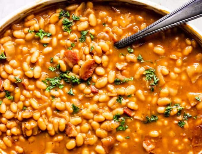 Overhead view of baking dish with baked beans, topped with fresh parsley as a garnish.