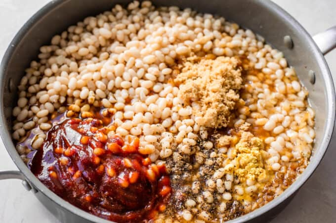 Large skillet filled with beans, topped with seasoning, molasses, bbq sauce, and brown sugar.