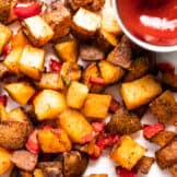 Baked, crispy breakfast potatoes mixed with red bell pepper and jalapeño spread onto a piece of parchment paper served with a cup of ketchup.