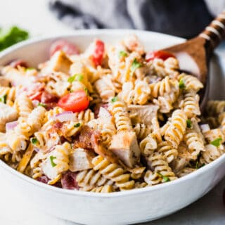 White bowl filled with homemade chicken pasta salad with a wooden serving spoon.