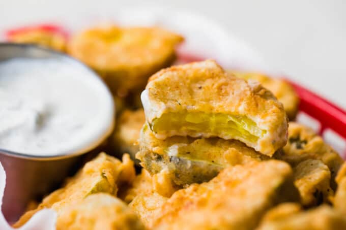 Horizontal image of a fried pickle with a bite taken out and showing the pickle inside of the fried exterior.