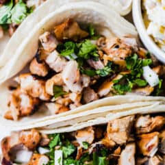 Up close image of diced up grilled chicken in soft white corn tortillas topped with diced white onion and cilantro. A bowl of street corn on the side.
