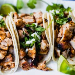 Grilled chicken street tacos laid next to each other with wedges of lime off to the side.