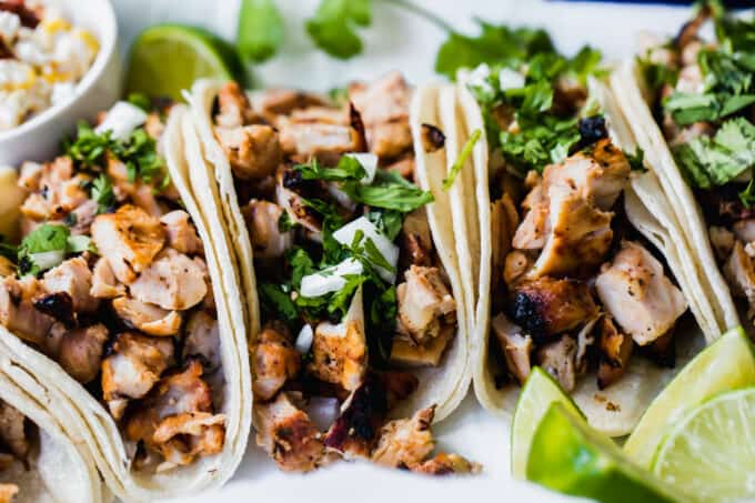 Grilled chicken street tacos laid side by side with wedges of lime to the side.