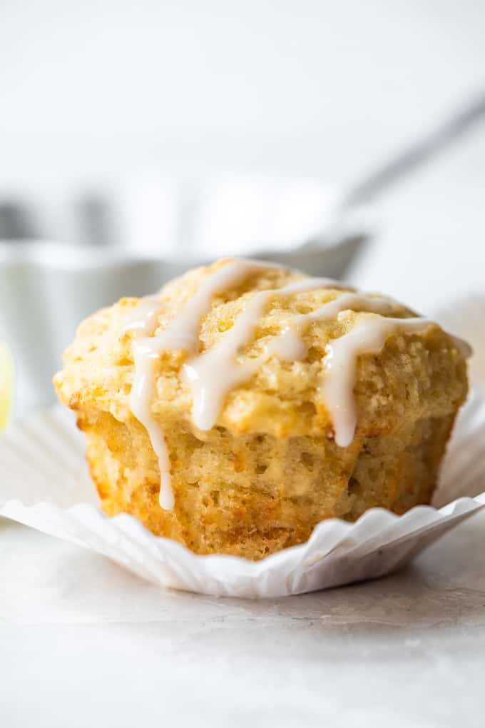 Lemon muffin sitting in a white cupcake liner, with a light white drizzle on top. Bowl of icing with a spoon behind the muffin.