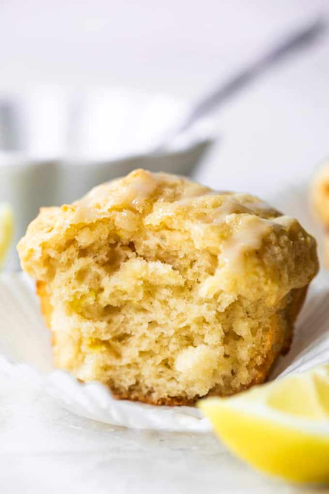 Lemon muffin in a white paper, with a bite missing showing the texture of the baked muffin.